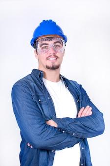 Der junge arbeitnehmer des porträts, der mit den armen lächelt, kreuzte lokalisiert