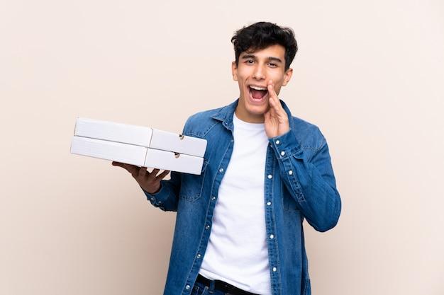 Der junge argentinische mann, der pizzas über lokalisierter wand schreit mit dem breiten mund hält, öffnen sich