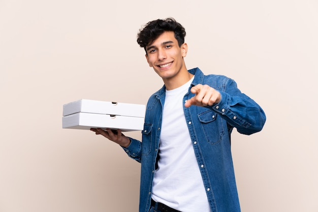 Der junge argentinische mann, der pizzen über lokalisierter wand hält, zeigt finger auf sie mit einem überzeugten ausdruck