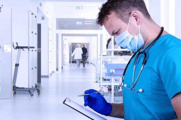 Der junge arzt in medizinischer kleidung untersucht die krankengeschichte und macht sich mit einem stift notizen. medizinisches konzept