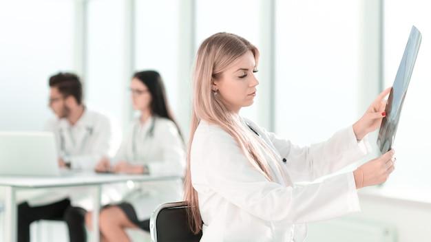 Der junge arzt sieht sich das röntgenbild des patienten mit kopierraum an