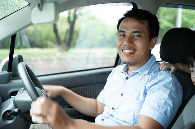 Der junge asiatische fahrer lächelt, wenn er ein auto fährt