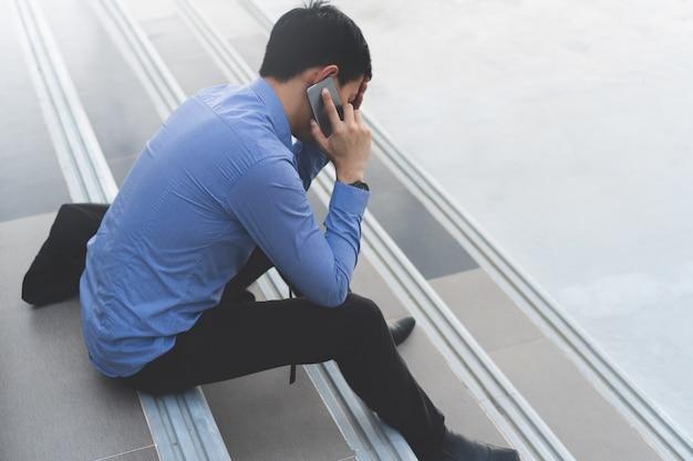 Der junge asiatische geschäftsmann, der auf der treppe spricht am telefon sitzt, betonen.