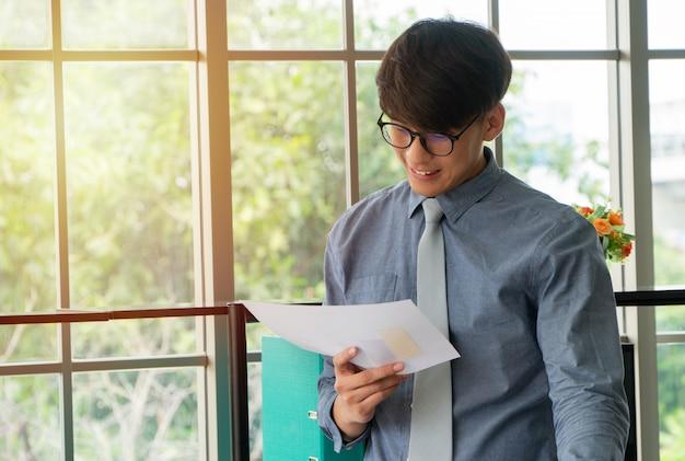 Der junge asiatische geschäftsmann, der aufgeregt wird, glücklich und erfolg an dem arbeitsplatz feiernd, sehen, den jährlichen verkaufsbericht abzuschließen