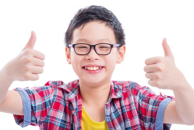 Der junge asiatische junge, der sich daumen zeigt und lächelt über weißem hintergrund