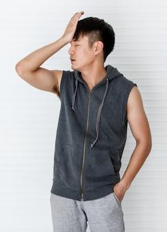 Der junge asiatische mann, der ärmelloses t-shirt trägt, graue sportbekleidung, die handstirn hält, zeigen fehler, versagen im weißen hintergrund.
