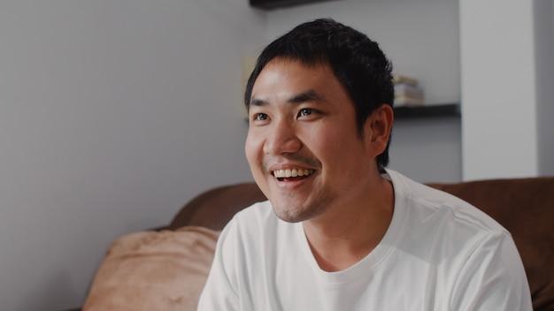 Der junge asiatische mann, der den steuerknüppel spielt videospiele im fernsehen im wohnzimmer verwendet, der mann, der unter verwendung glücklich sich fühlt, entspannen sich die zeit, die zu hause auf sofa liegt. männer spielen zu hause entspannen.