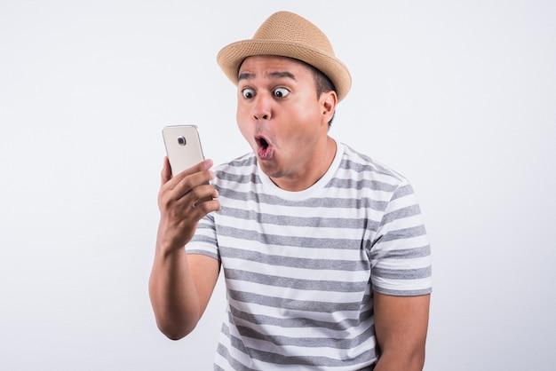 Der junge asiatische mann, der smartphone schaut und glaubt schock