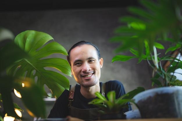 Der junge asiatische mann freut sich über die wachsende pflanze in einem kleinen grünen garten zu hause, den hobby-lebensstil mit grüner natur in einem haus, den blumenbaum im topf zum botanischen gartenbau in der landwirtschaft
