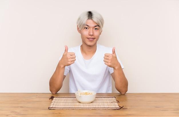 Der junge asiatische mann mit dem ramen in einer tabelle gebend daumen up geste
