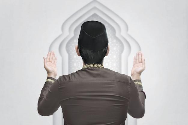 Der junge asiatische moslemische mann, der hand anhebt und beten
