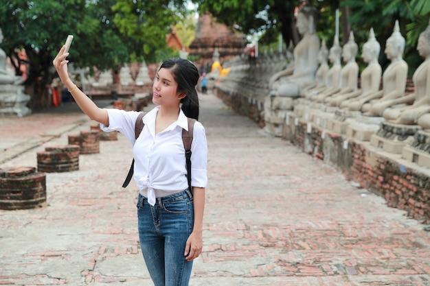Der junge asiatische reisende, der handy verwendet und tun selbstporträt im tempel beim reisen während der feiertagsferien