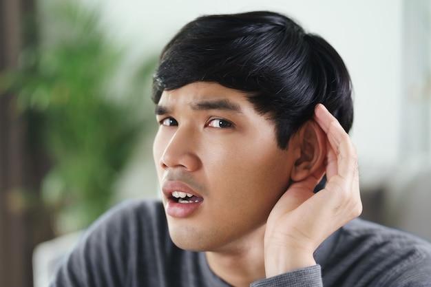 Der junge asiatische taube behinderte mann mit hörproblemen hält seine hand über das ohr, hört aufmerksam zu, schwerhörig.