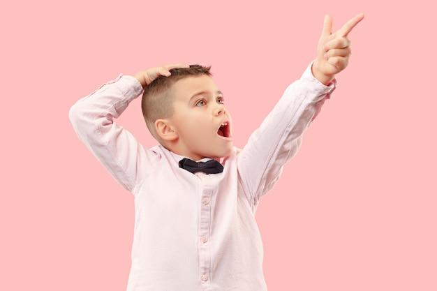 Der junge attraktive jugendlich junge, der überrascht auf rosa lokalisiert aussieht