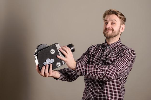 Der junge attraktive kameramann in einem karierten hemd zieht sich zu einer alten filmkamera zurück