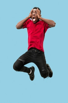 Der junge attraktive mann, der beim springen überrascht aussieht