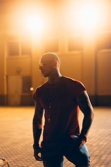 Der junge, attraktive mann posiert nachts vor der kamera