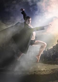 Der junge attraktive moderne balletttänzer in der schwarzen jacke über altem kirchen- und rauchhintergrund.