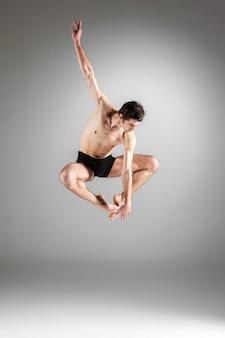 Der junge attraktive moderne balletttänzer springt auf weiße wand