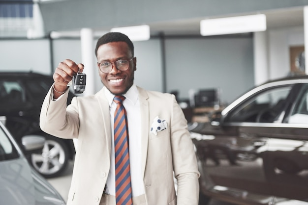 Der junge attraktive schwarze geschäftsmann kauft ein neues auto, er hält die schlüssel in der hand. träume werden wahr