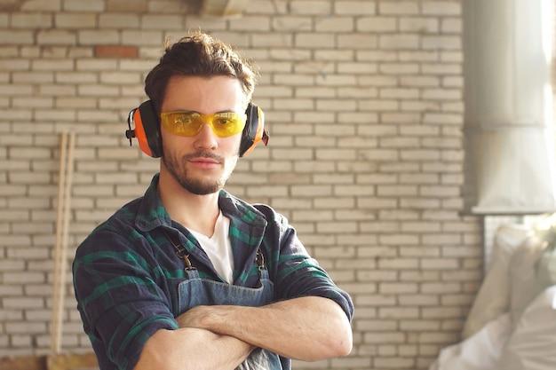 Der junge attraktive uniformierte zahler schaut mit verschränkten armen in die kamera