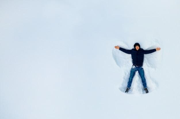 Der junge auf einem schneeengel zeigt