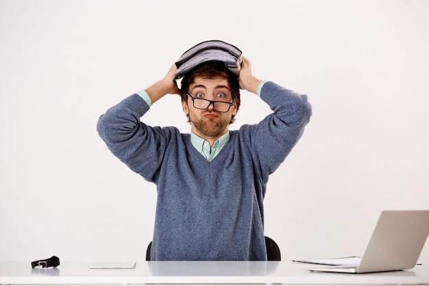 Der junge bärtige angestellte, ein mann, der im büro arbeitet, hat fristen, hält berichte und dokumente auf dem kopf, ist voller arbeit und sitzt in der nähe eines laptops