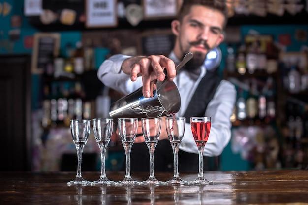 Der junge barkeeper demonstriert den prozess der zubereitung eines cocktails im nachtclub