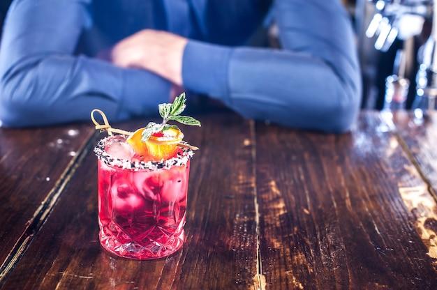 Der junge barkeeper fügt einem cocktail zutaten hinzu, während er in der kneipe in der nähe der theke steht