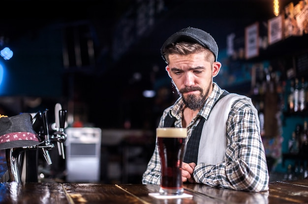 Der junge barmann demonstriert seine fähigkeiten über den ladentisch hinter der bar