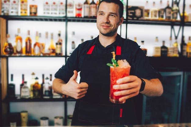 Der junge barmann hält ein glas kalten cocktails in der linken hand