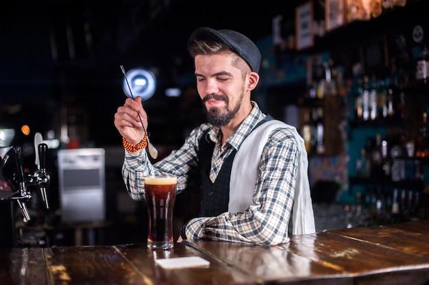 Der junge barmann macht einen cocktail, während er in der nähe der bartheke in der bar steht