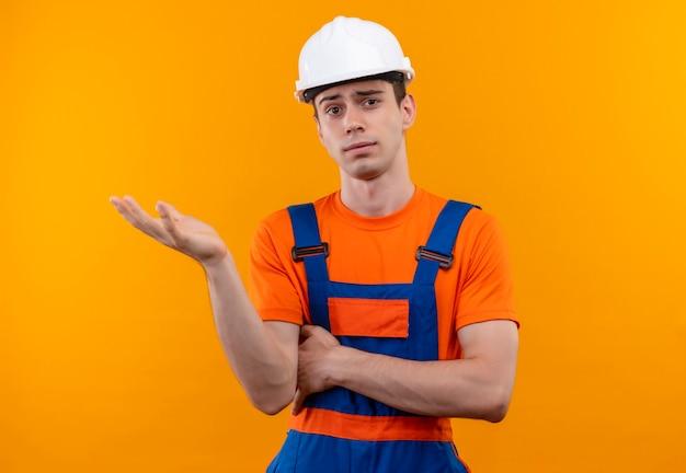 Der junge baumeister, der bauuniform und schutzhelm trägt, hält die linke hand hoch