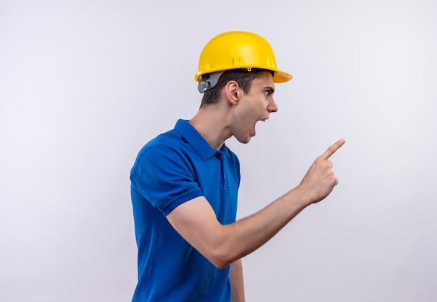 Der junge baumeister, der die bauuniform und den schutzhelm trägt, zeigt wütend mit dem zeigefinger nach links