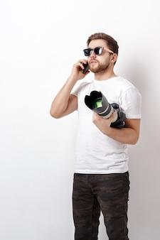 Der junge berufsfotograf in einem weißen hemd hält eine schwere digitalkamera mit einem langen objektiv und telefoniert mit einem kunden