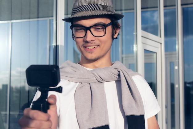 Der junge blogger mit hut und brille schießt ein vlog-video auf einer action-kamera.