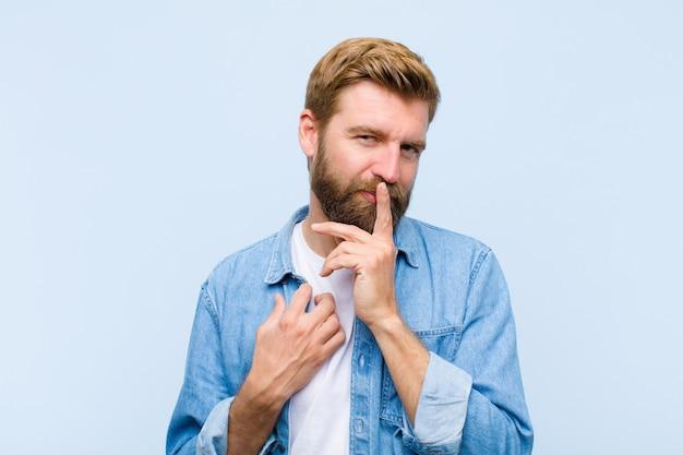 Der junge blonde erwachsene mann, der ernst und mit dem finger kreuzend schaut, drückte zu den lippen, die die ruhe fordern und hielt ein geheimnis