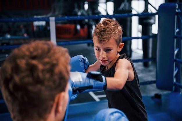 Der junge boxtrainer hilft dem kleinen jungen in schutzkleidung auf dem ring zwischen den runden.