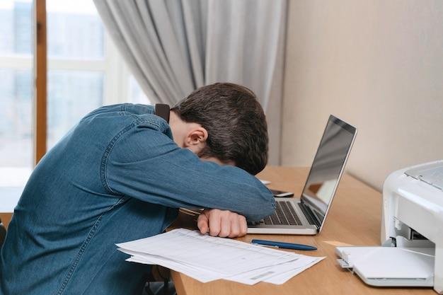 Der junge burnout-mann weint in seinem büro zu hause und sitzt mit einem laptop und dokumenten an seinem schreibtisch