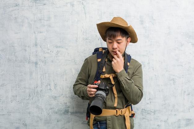 Der junge chinesische forschermann, der eine kamera hält, entspannte sich das denken an etwas an a