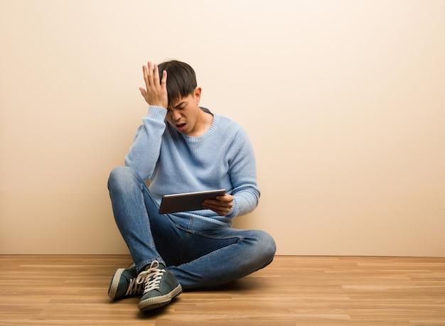 Der junge chinesische mann, der unter verwendung seiner vergesslichen tablette sitzt, verwirklichen etwas