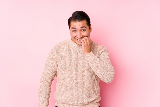 Der junge curvy mann, der in einer rosa wand aufwirft, lokalisierte die beißenden fingernägel, nervös und sehr besorgt.