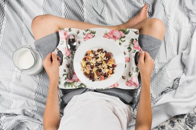 Der junge, der auf bett sitzt, bereiten vor, um am morgen zu frühstücken