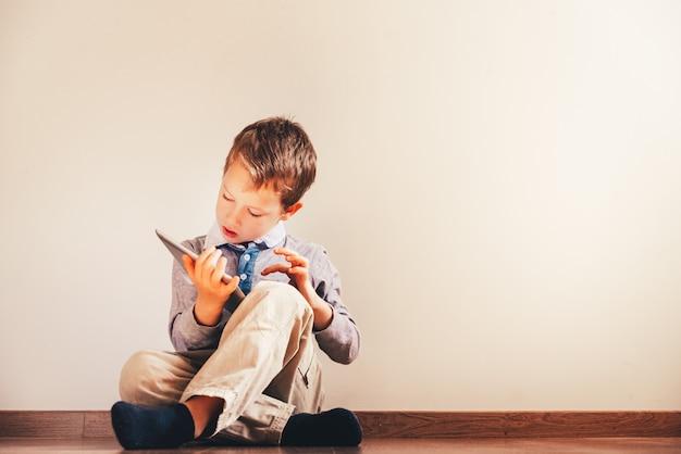 Der junge, der auf dem boden unter verwendung einer tablette sitzt, absorbierte in ihr.