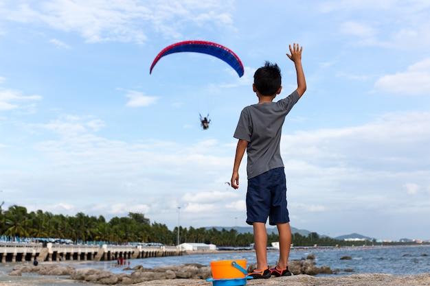 Der junge, der auf den felsenhänden steht, hob das oben betrachten motorgleitschirmfliegen an