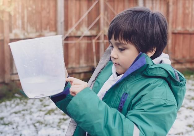 Der junge, der den messenden krug zeigt auf das niveau des regens hält, sammelte im garten. 6 jahre altes kind misst niederschlag für schulforschungsprojekt über wetter und klimawandel. bildungskonzept