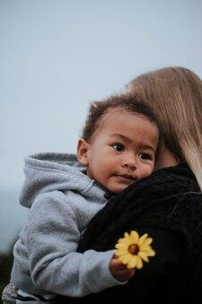Der junge, der eine blume hält, trug von seiner mamma