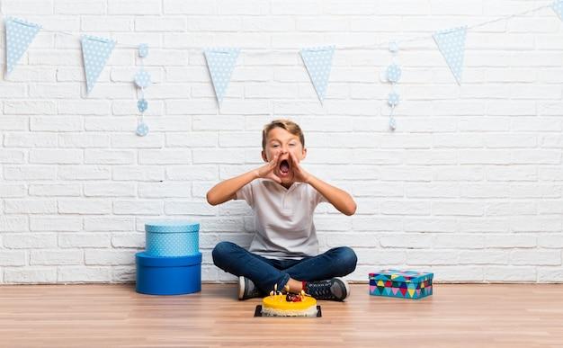 Der junge, der seinen geburtstag mit einem kuchen feiert, der mit dem breiten mund schreit, öffnen sich