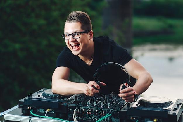 Der junge dj-hipster befindet sich hinter dem mischpult und hält kopfhörer