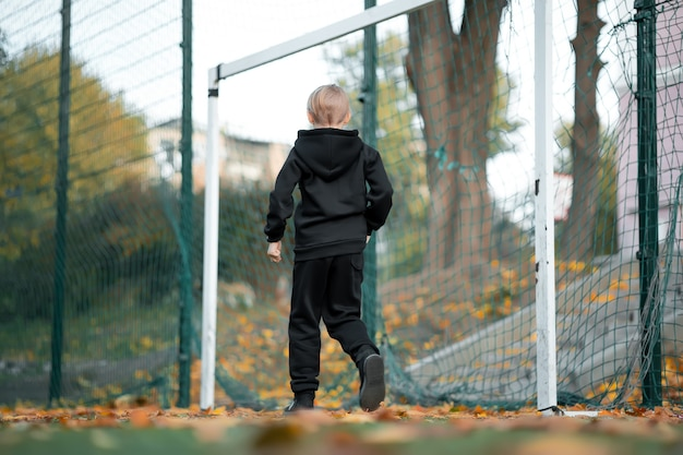 Der junge eines sportlers steht am tor und wartet auf den ballaufschlag.